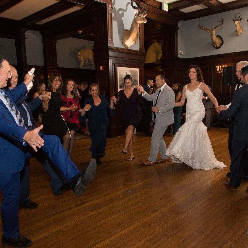 wedding guests kick legs out while dancing in semi circle