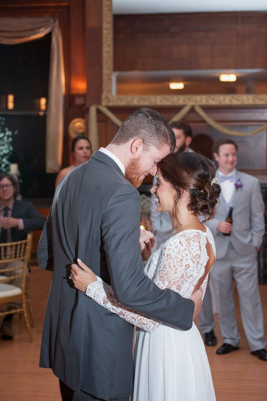 bride and groom put heads together during first dance