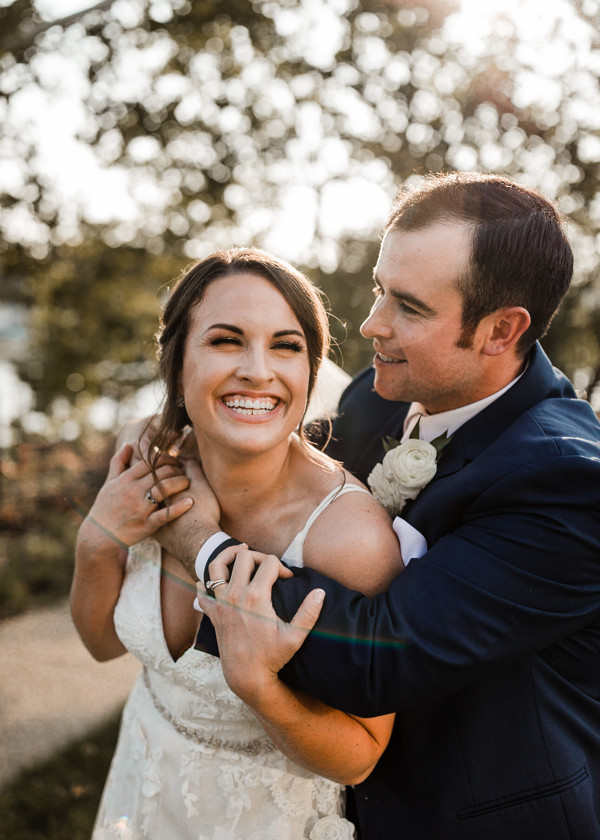 bride and groom smile while holding each other