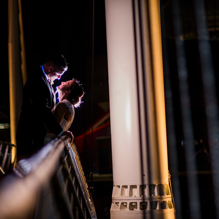 bride and groom pose during night shot on foot bridge