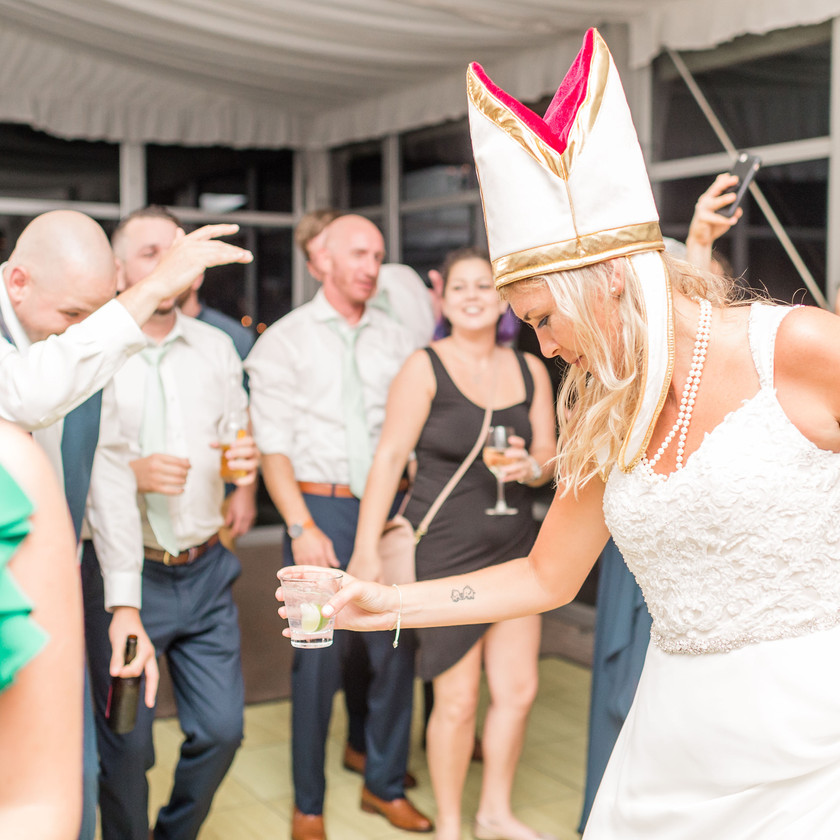 bride wears pope hat mitre while dancing