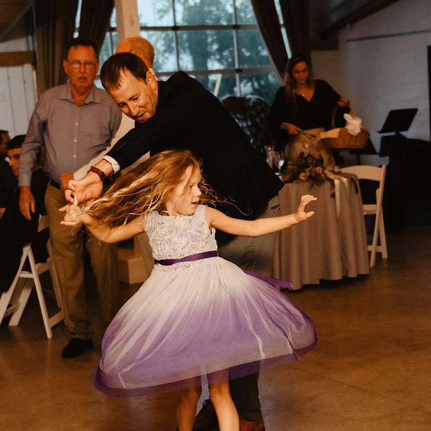girl in dress is spun on dance floor