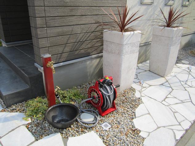 【白い石張りの中に映える赤色の立水栓とホースリール】