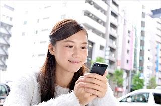 微笑みながらスマートフォンを見る女性
