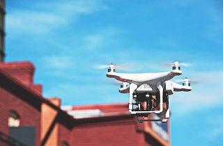 赤いレンガの建物の横を飛ぶドローン