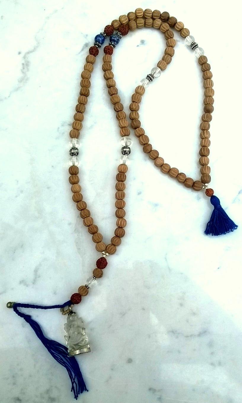 Silver Sandal Mala - Una mala con perle di Legno di Sandalo, Cristallo, Lapislazzulo, Rudraksha, Argento e pendente di Ganesh di Cristallo intagliato a mano.