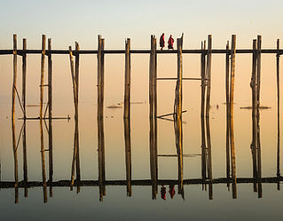 Reflection of Monks Crossing a Wooden Br