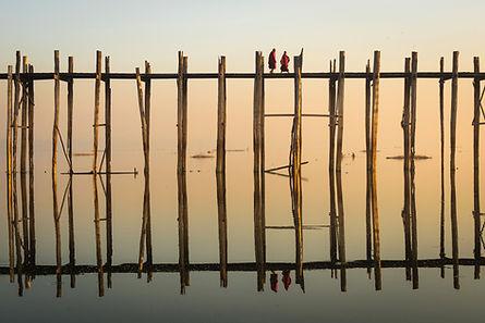 Reflejo de monjes cruzando un puente de