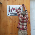 Hanging the new sign on the sugar shack.