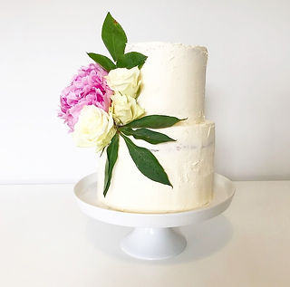 Two tier white wedding cake with pink peony and white roses
