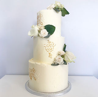 Three tier white wedding cake with stenciled roses, decorated with fresh roses and leaves