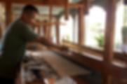 artesano tejiendo en telar de pedal con