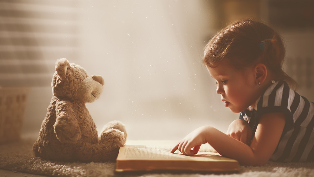boy reading to teddy