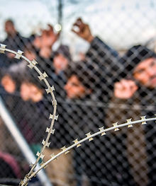 Refugees waiting behind barbed wire fenc