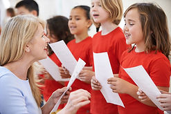 Children In Singing Group Being Encourag