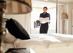 Chambermaid carrying linen in hotel bedr