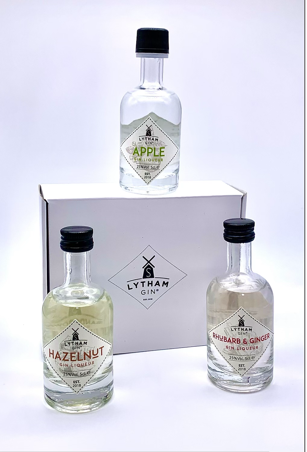 Three small bottles of gin on a white box