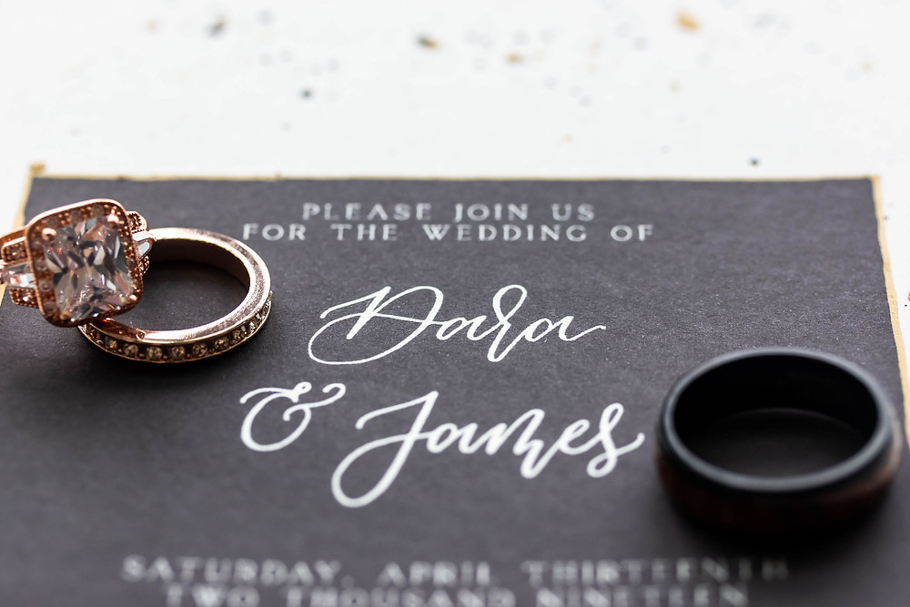 Detail shot of wedding invitation and rings at Noah Liff Opera Center