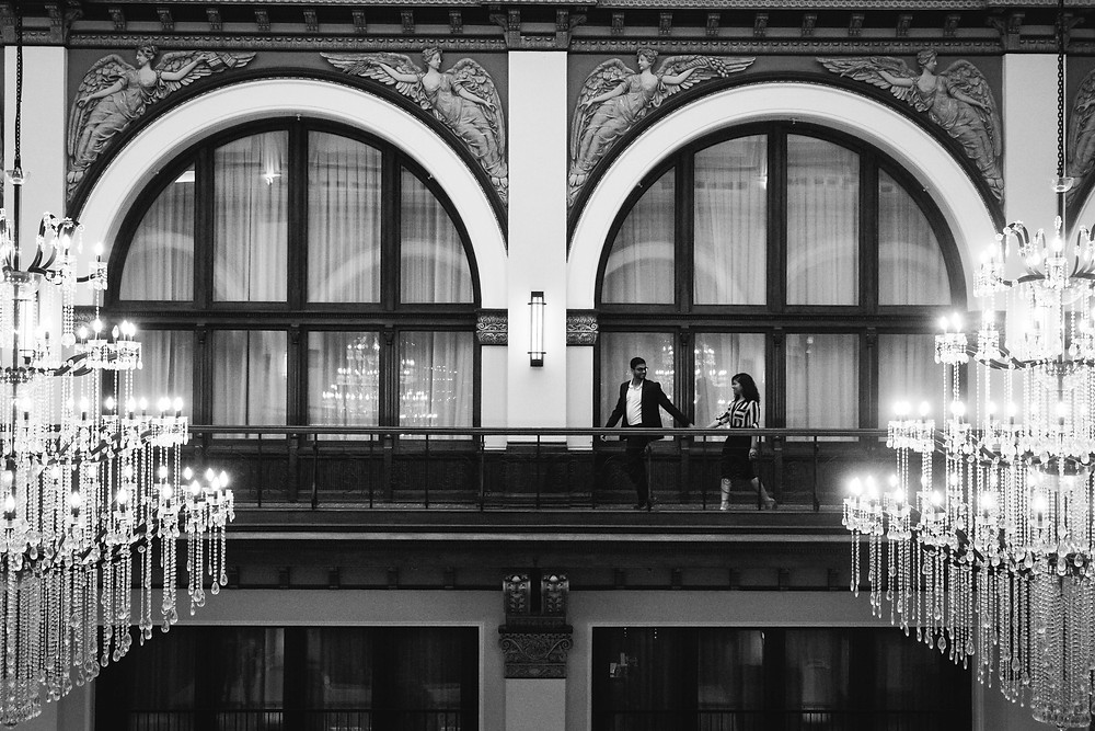 Black and white cute couple walks across hotel lobby at Union Station Hotel