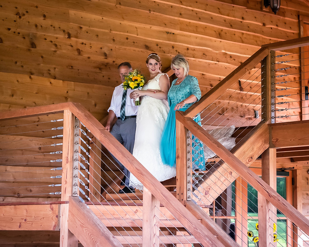Bride walks down the staircase at Sycamore Farm