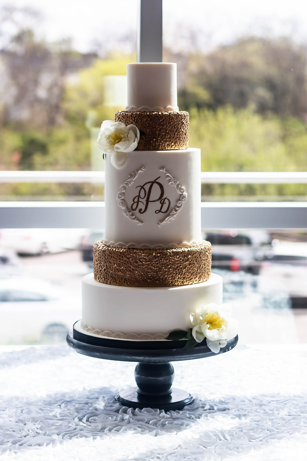 Detail shot of white and gold wedding cake at Noah Liff Opera Center