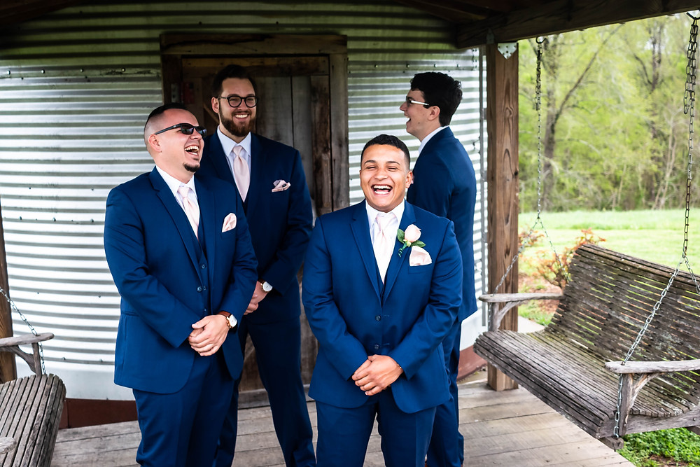 Groom shares laugh with other groomsmen at Owen Farm