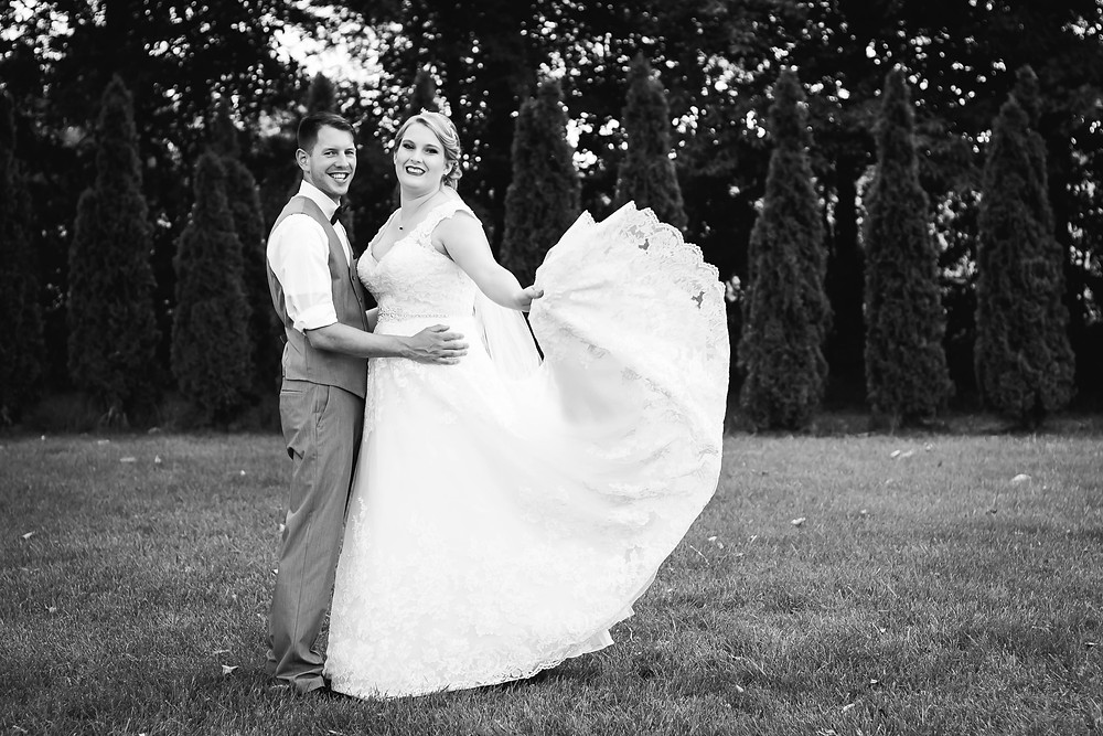 Black and white bride and groom play with wedding dress in the wind at Sycamore Farm