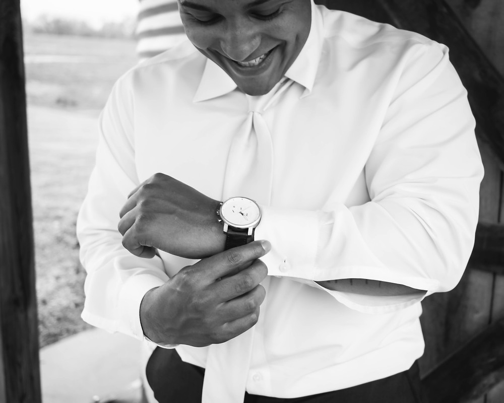 Black and white groom getting ready with watch at Owen Farm