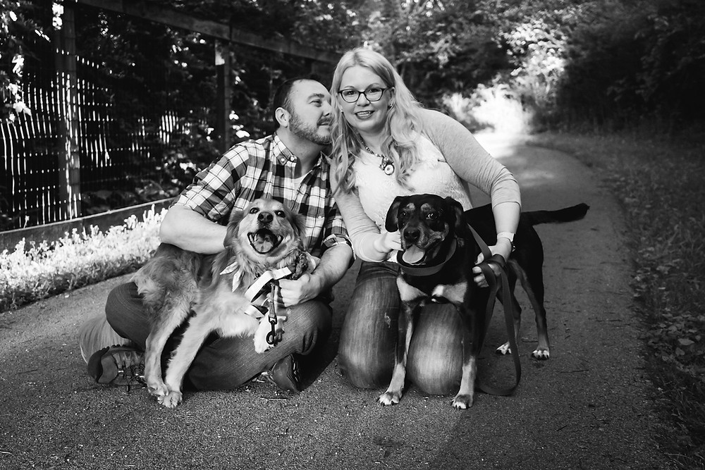Black and white cute couple pose for pictures with dogs on path at the Nashville Greenway