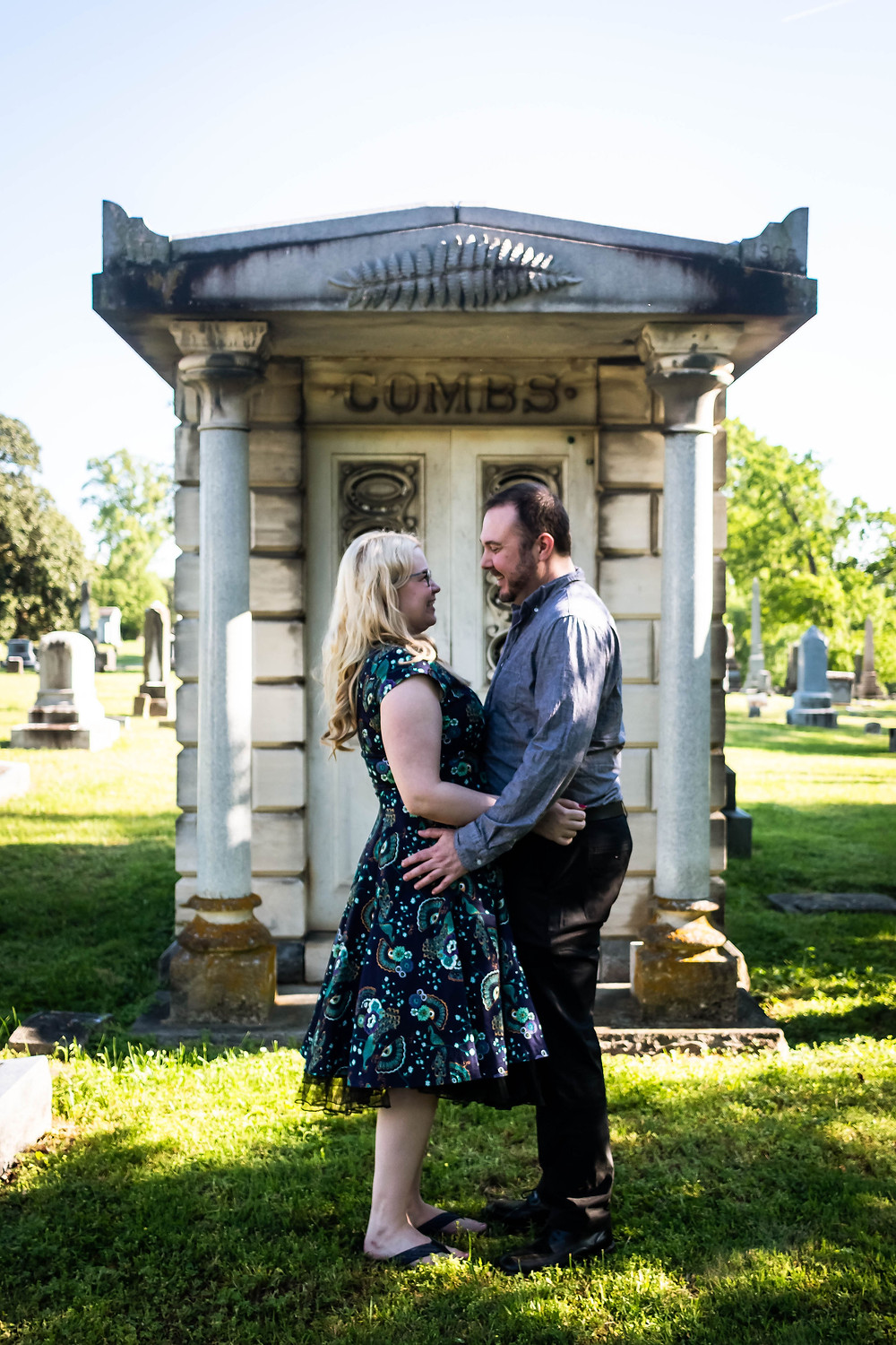 Cute couple face each other in front of a mausoleum at Mt. Olivet Cemetery