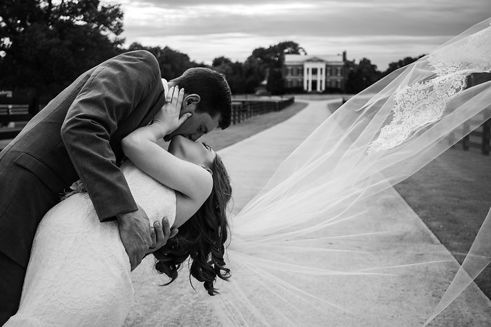 Black and white bride and groom dip kiss