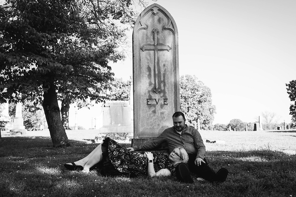 Black and white cute couple lay down at the base of a headstone at Mt. Olivet Cemetery