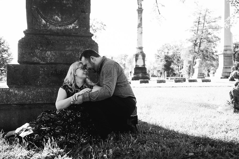 Black and white cute couple at base of headstone at Mt. Olivet Cemetery