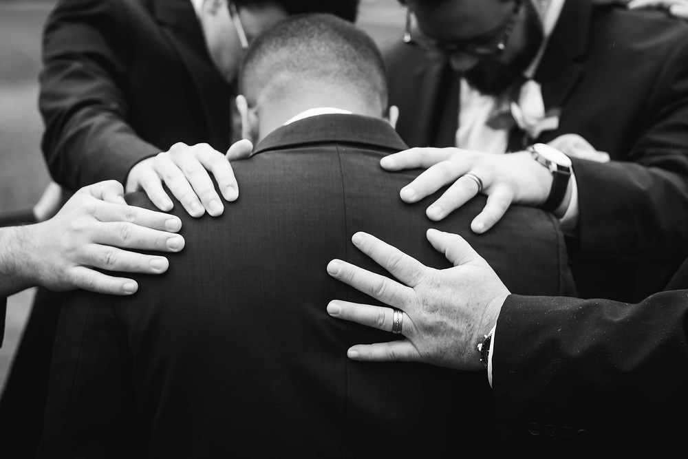 Groomsmen lay hands on groom before ceremony at Owen Farm