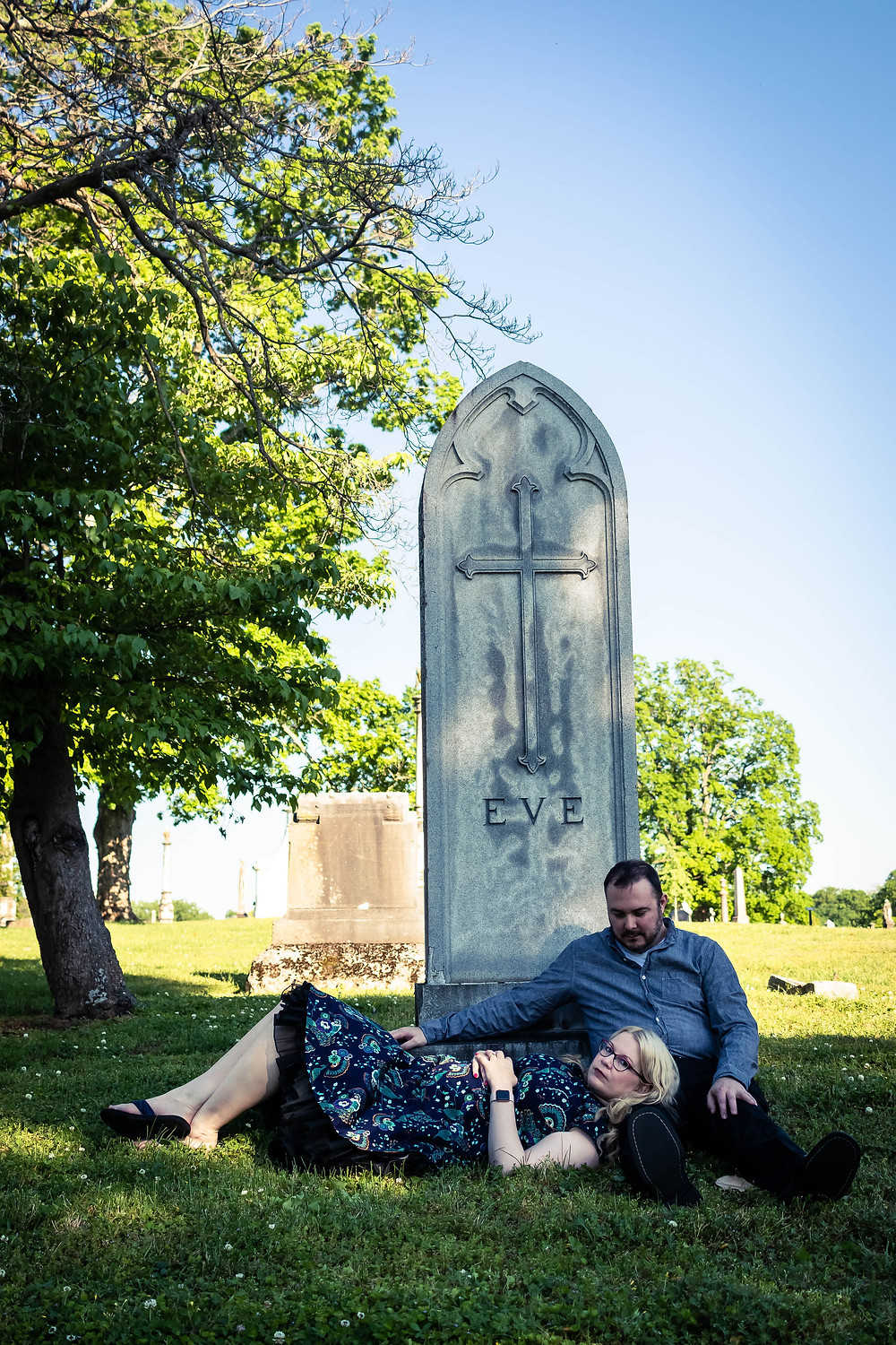 Cute couple lay down at the base of a headstone at Mt. Olivet Cemetery