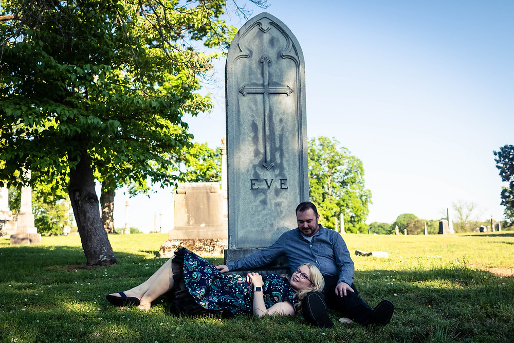Cute couple laying down at the base of a headstone at Mt. Olivet Cemetery