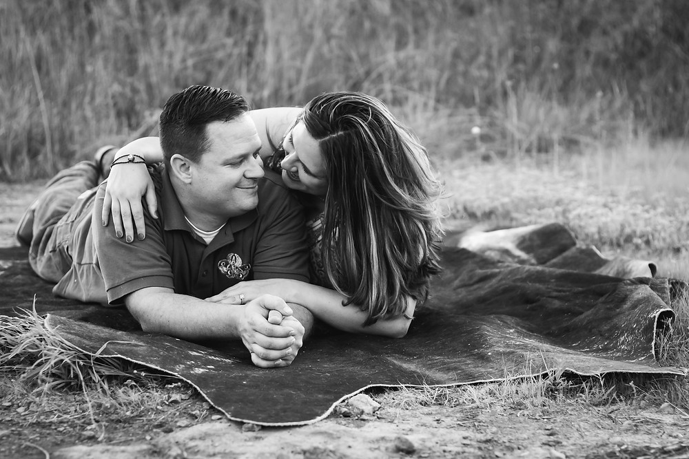 Black and white cute couple laying in field in Lewisburg, Tennessee
