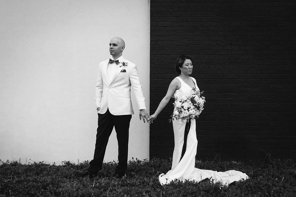 Black and white bride and groom against black and white wall at Noah Liff Opera Center