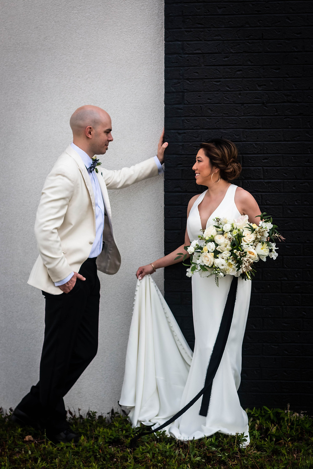 Bride and groom facing each other against black and white wall at Noah Liff Opera Center