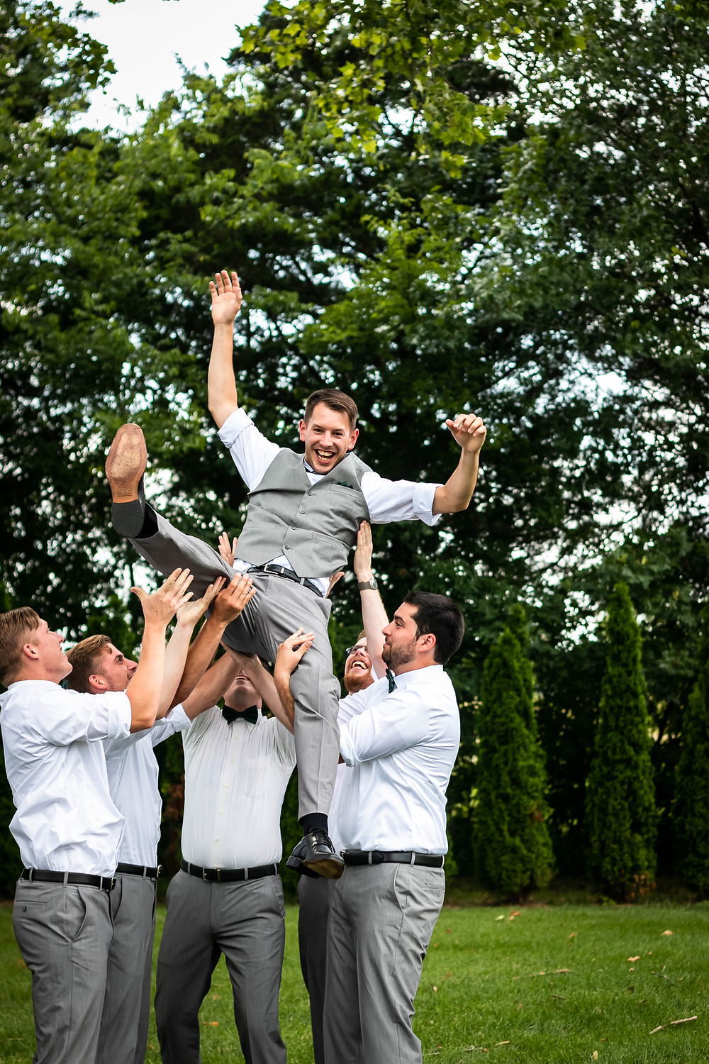 Groom being tossed in the air by groomsmen at Sycamore Farm