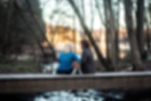 Cute couple chatting seated on a bridge in nature