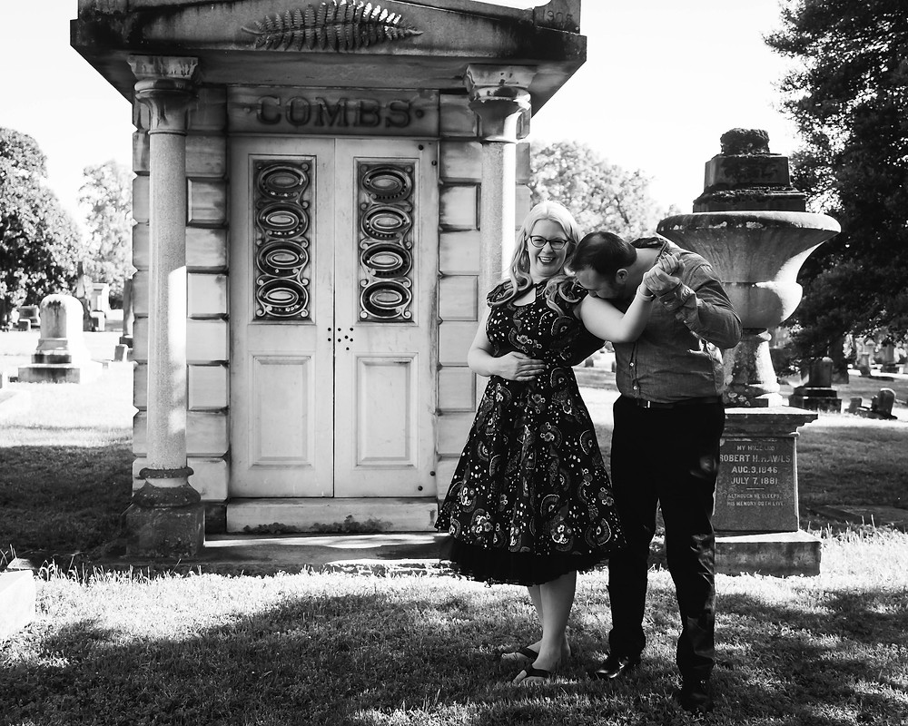 Black and white cute couple kiss in front of a mausoleum at Mt. Olivet Cemetery