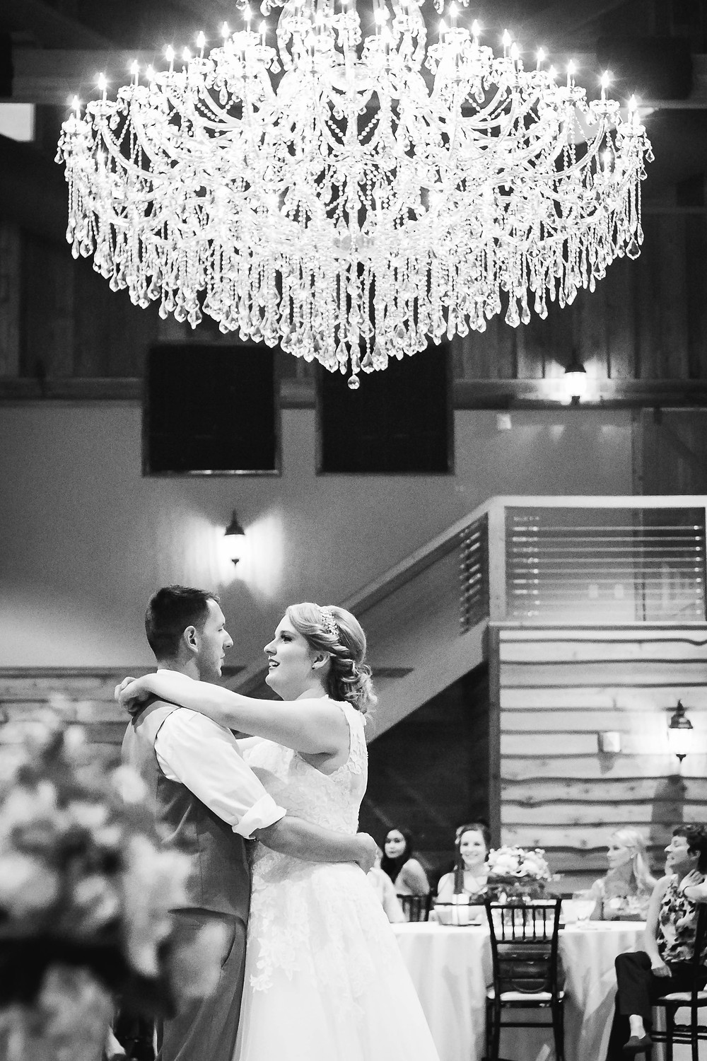 Black and white bride and groom first dance under chandelier at Sycamore Farm