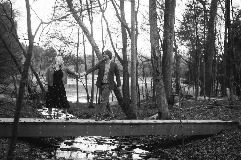Black and white cute couple walk across a bridge at Long Hunter State Park