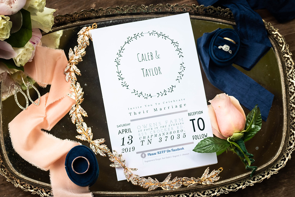 Detail shot of wedding invitation, flowers, and rings at Owen Farm