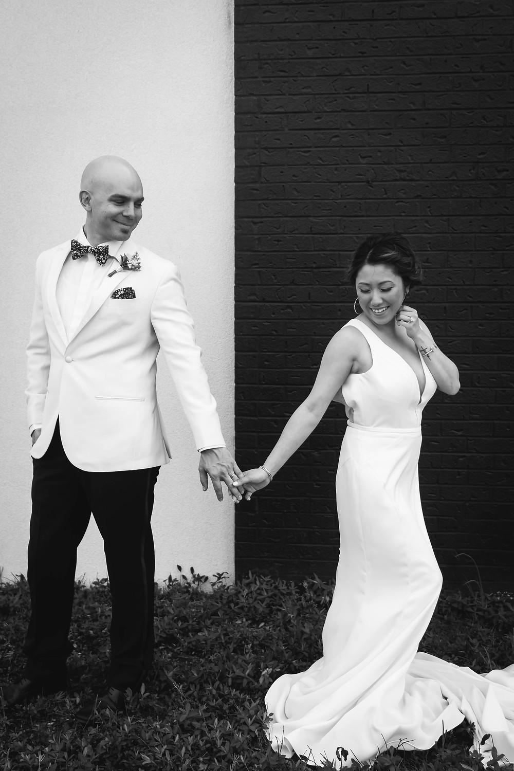 Black and white bride and groom holding hands at Noah Liff Opera Center