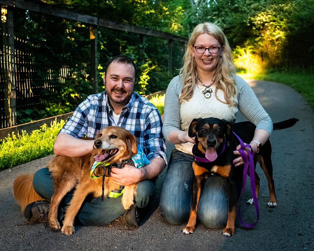Cute couple poses with dogs on a path at the Nashville Greenway