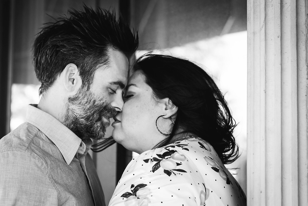 Black and white cute couple share a kiss downtown in downtown Murfreesboro