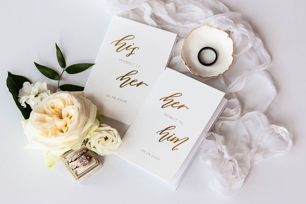 Detail shot of his and hers wedding vow books and rings at Noah Liff Opera Center