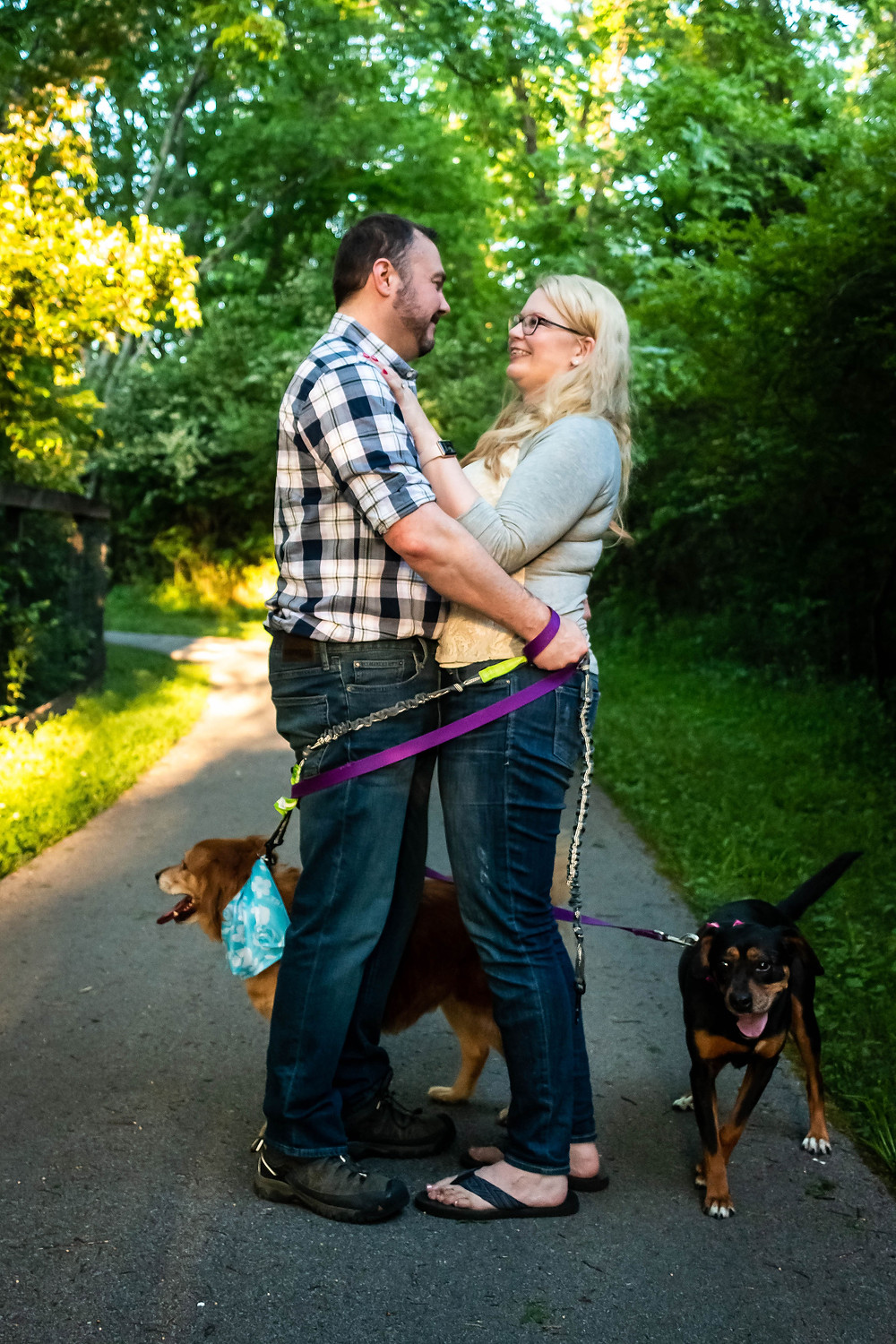 Cute couple face each other wrapped up in dog leashes at the Nashville Greenway